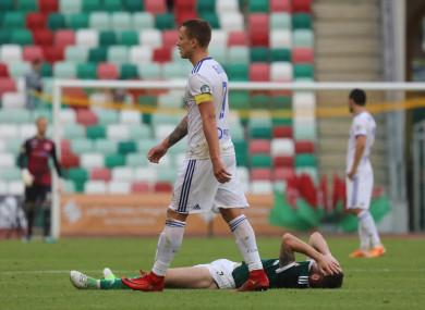 Artem Bykov walks by a dejected Jamie McDonagh