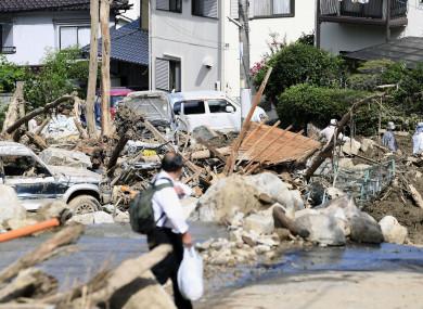 A man walks past debris from a heavy rain in Hiroshima, southwestern Japan