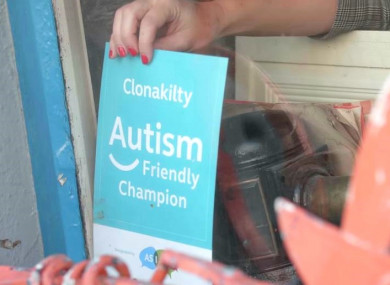 An 'Autism Friendly Champion' sign in the window of a local business in Clonakilty.