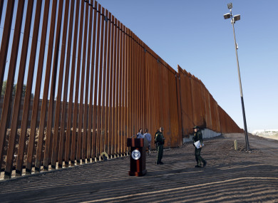 Border Patrol agents and others stand next to a new stretch of border wall in Calexico, California