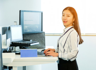 A woman standing at a desk