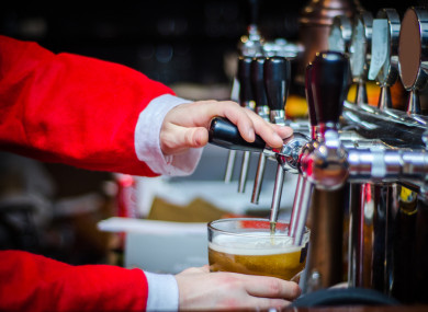 File photo of a man dressed as Santa Claus pulling a pint.