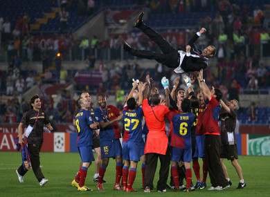 The Barca players fling Guardiola into the air.