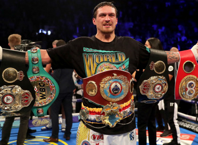 Oleksandr Usyk celebrates with the hardware after beating Tony Bellew.