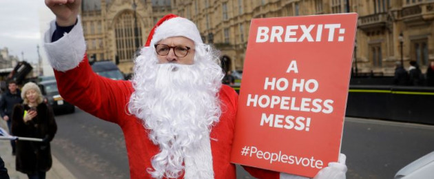 A pro-European Union protester dressed as Santa Claus holds a placard across the street from the Houses of Parliament in London.