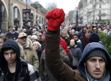A man with his hand wrapped in a red scarf takes part in a rally in Paris.