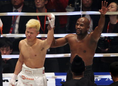 Floyd Mayweather holds up Tenshin Nasukawa's hand after their New Year's Eve bout in Tokyo.