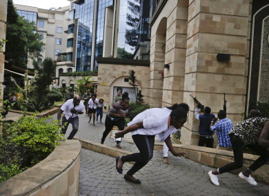 Civilians flee as security forces aim their weapons at the buildings of a hotel complex in Nairobi, Kenya, yesterday.