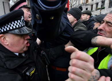 Police officers scuffle with pro-Brexit demonstrators at Trafalgar Square, London, yesterday.