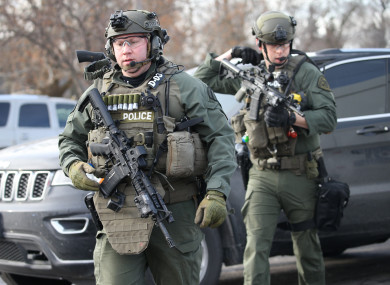 Police officers armed with rifles stage near a building where the shooting took place