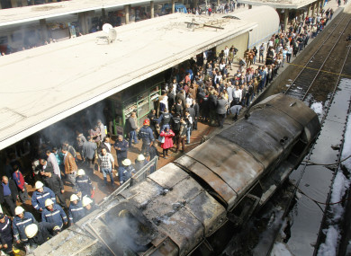 Rescue workers stand next to a burnt out wagon on the railway tracks after a fire caused deaths and injuries at the main train station in Cairo.