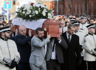 Ian Ogle's coffin is carried past the scene of his murder in East Belfast on Monday.