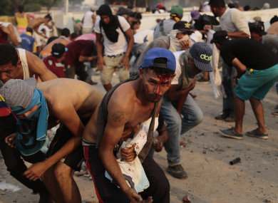 Injured demonstrators take cover at the Colombian border