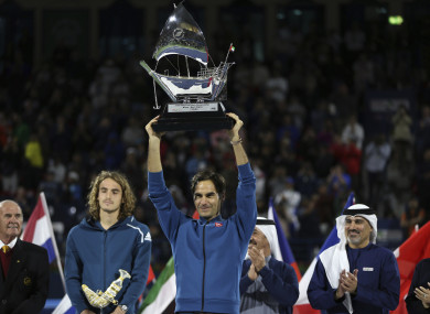 100 not out: Federer lifts the trophy.