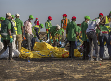 Workers collect clothes and other materials, under the instruction of investigators, at the scene where the Ethiopian Airlines Boeing 737 Max 8 crashed last week
