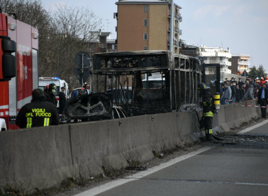 Firefighters stand by the gutted remains of the bus in San Donato Milanese, near Milan.