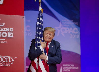 US President Donald Trump hugs the US flag during CPAC yesterday.