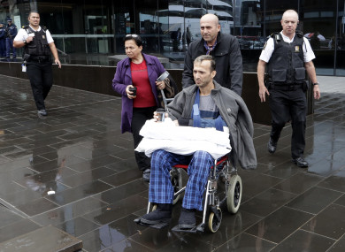 Survivor Temel Atacocugu (centre) is escorted from outside the High Court in Christchurch, New Zealand, today.