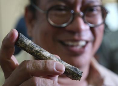 Filipino archeologist Armand Salvador Mijares shows a femur bone discovered in the cave.
