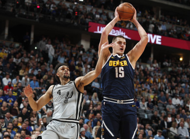 Denver Nuggets center Nikola Jokic, right, pulls in a rebound.