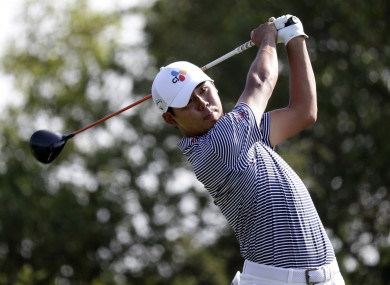 Si Woo Kim hits watches a shot on the 15th hole.