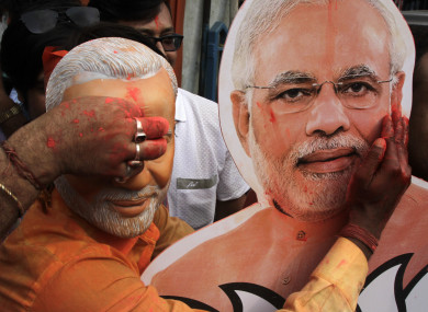 A Bharatiya Janata Party (BJP) supporter puts vermillion powder on a cutout of Narendra Modi during celebrations of the party's victory in Kolkata , India