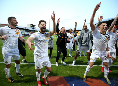 Newport County players and manager Michael Flynn celebrate their win.