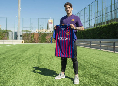 Reis holds up the Barca shirt.