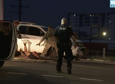 In this image made from video, police proceed to apprehend a suspect on the ground next to a white truck,