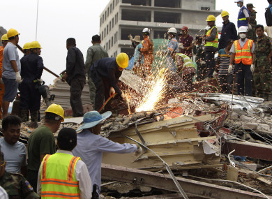 Rescuers try to remove the rubble at the site of the collapsed building.