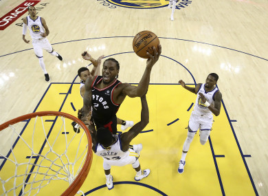 Toronto Raptors forward Kawhi Leonard shoots against the Golden State Warriors during the first half of Game 3 .