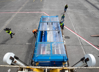 Tanks carrying two Beluga Whales are inspected as they are unloaded from an aircraft in Iceland