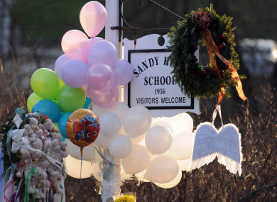 2012 file photo, flowers, teddy bears, candles, balloons and a pair of angel wings left by mourners are seen at the Sandy Hook Elementary School sign