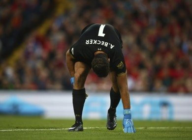 Liverpool's goalkeeper Alisson Becker holds his leg.