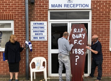Former director Joy Hart, handcuffed to the main stand, pleads for help to save Bury as fans deliver a symbolic coffin.
