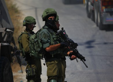 Israeli soldiers stand guard near the scene in the settlement of Migdal Oz.