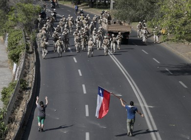 Demonstrators challenge soldiers as a state of emergency remains in effect in Santiago, Chile.