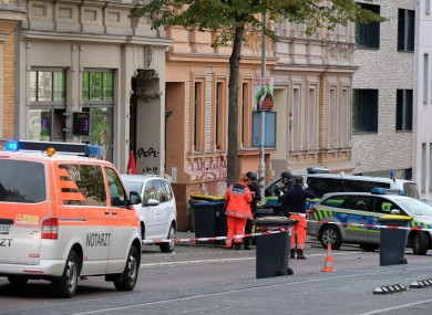 Policemen and rescue workers standing on the street in Halle.