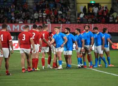 Wales and Uruguay players shake hands after their pool match.