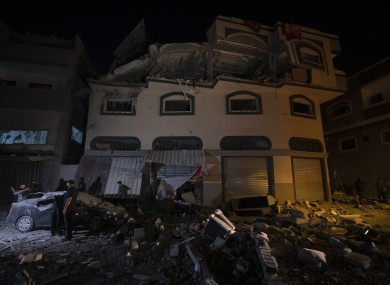 Palestinians check the damage of a house targeted by Israeli missile strikes in Gaza City.