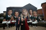 Sinn Fein John Finucane, candidate Elisha McCallion and Vice President of Sinn Fein Michelle O'Neill beside a mural of the Derry Girls.