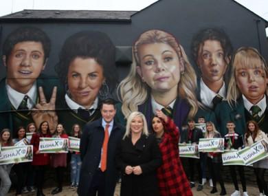 Sinn Fein John Finucane, candidate Elisha McCallion and Vice President of Sinn Fein Michelle O'Neill beside a mural of the Derry Girls.