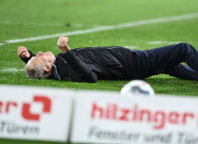 Christian Streich pictured on the ground after being pushed over by David Abraham.