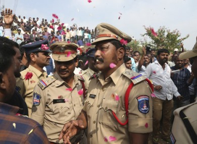 People throw flower petals on Indian policemen after the men were shot.