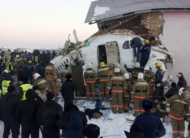 Police and rescuers work on the side of a plane crash.