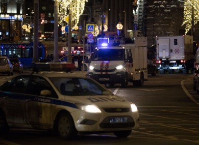 Police vehicles are seen on the site of a shooting in central Moscow