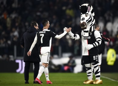 Cristiano Ronaldo (L) of Juventus FC shakes hands with Jay (mascotte of Juventus FC).