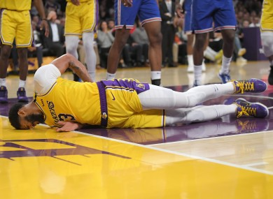 LA Lakers forward Anthony Davis winces as he hits the ground after falling while trying to defend against a shot by New York Knicks forward Julius Randle.