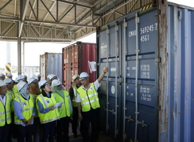 Malaysia's Environment Minister inspects a container of waste.