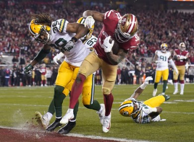 San Francisco 49ers running back Raheem Mostert, center right, scores a touchdown next to Green Bay Packers cornerback Tramon Williams.